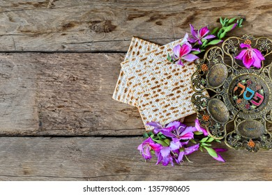 """Pesah celebration concept (Jewish Passover holiday). Vintage traditional seder plate and matzoh. In the central circle of the plate is written in Hebrew """"Pesah"""" ."""