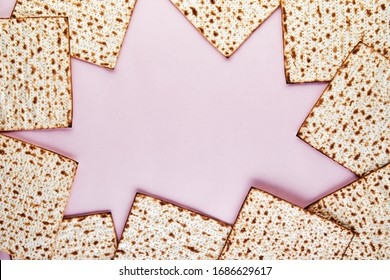 Pesah celebration concept - jewish Passover holiday. Matzo background on a pink background. View from above. Flat lay. Copy space.