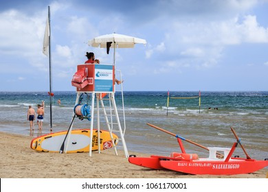 Pesaro, Marche, Italy - June 15, 2017: Beach on the adriatic sea. In the foreground is the lifeguard tower. Lifeguard watching people floating in the sea.