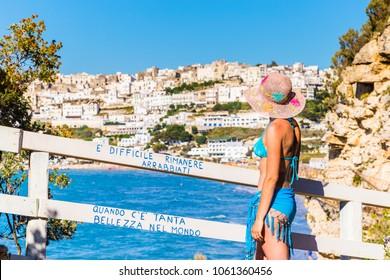 Peschici, apulia, italy, 29 May 2017. Woman in bikini admires the splendid panorama of Peschici, old town in Apulia region, south  Italy