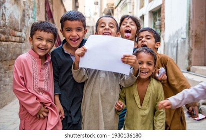 Peshawar, KP, Pakistan, May 25, 2017: Smiling kids hold blank sign