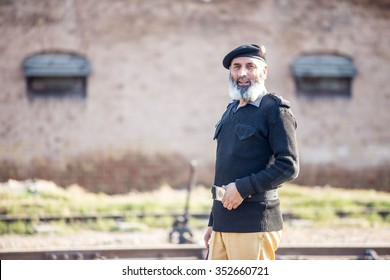 Peshawar, Pakistan - 9/27/2015  :  Pashtun policeman from the Khyber Pukhtoonkhwa province stands guard wearing grey uniform, black beret with Frontier Police insignia bearing the rail way .
