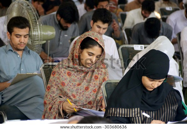 PESHAWAR, PAKISTAN - AUG 06: Students are busy in solving their question paper during aptitude test of University of Engineering and Technology, on August 06, 2015 in Peshawar.