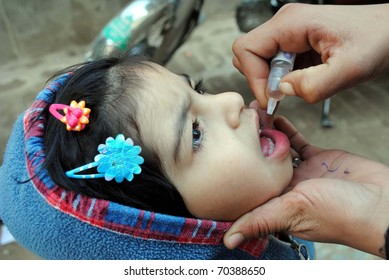 PESHAWAR, PAKISTAN - FEB 02: Unidentified child receives anti-Polio vaccination drops by health worker on occasion the anti-Polio campaign on February 02, 2011in Peshawar.