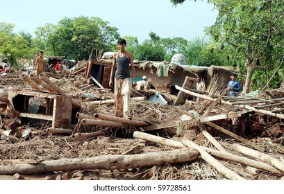 PESHAWAR, PAKISTAN - JUL 31: People remove household items from their collapsed house after flood water has passed the Pabbi area on July 31, 2010 in Peshawar, Pakistan.