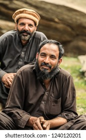 Peshawar, Pakistan - June 02, 2018: Old Two Men in Traditional Hat sitting near the Road in the mountains