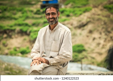 Peshawar, Pakistan - June 02, 2018: Old Old Men in Traditional Dress sitting near the Road in the mountains