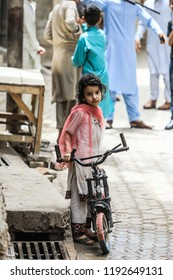 Peshawar, Pakistan - June 09, 2018: Young Happy Girl with the Bicycle on the Pakistanian Street