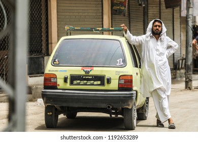 Peshawar, Pakistan - June 09, 2018: Pakistanian Taxi Driver in the Traditional Clothers on the Street