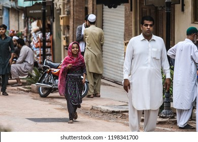 Peshawar, Pakistan - June 09, 2018: Young Pakistanian Girl in the Traditional Dress walking on the Street