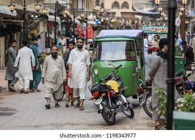 Peshawar, Pakistan -June 09, 2018: Rickshaw and Bike on the Crowded street