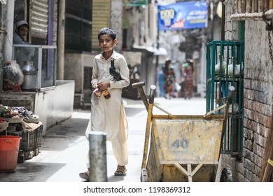 Peshawar, Pakistan - June 09, 2018: Teenager with toy gun playing on the street