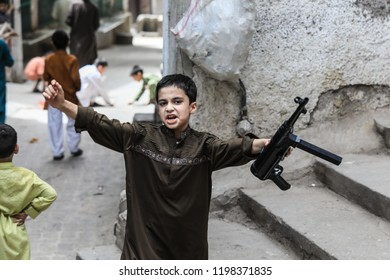 Peshawar, Pakistan - June 09, 2018: Young Boy with toy gun playing on the street