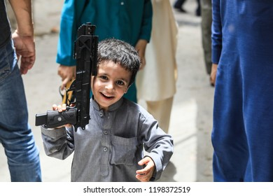 Peshawar, Pakistan - June 09, 2018: Young Happy Boy with toy gun playing on the street and Laughing