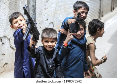Peshawar, Pakistan - June 09, 2018: Young Happy Boys with toy guns playing on the street and Laughing