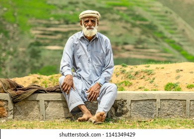 Peshawar, Pakistan - June 10, 2018: Pashtun Old Man in Pakol sitting near the Road