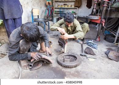 PESHAWAR, PAKISTAN - May 24: A child labor and has mechanics teacher repairing Track Break lather in local Mechanics markets., on 24 May, 2016 Peshawar