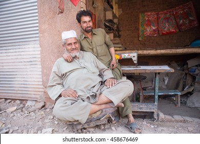 PESHAWAR, PAKISTAN - May 24: An old man has happy mod but has mechanic student also in Mechanics shop, on 24 May, 2016 Peshawar