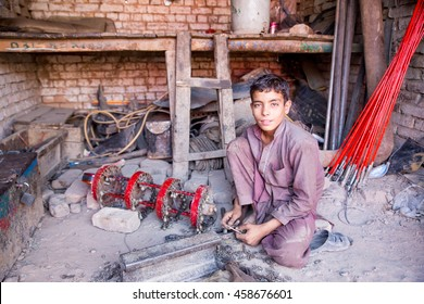 PESHAWAR, PAKISTAN - May 24: A Young Child making decorating things to big car by hand or handy craft in Local Market workshop, on 24 May 2016 Peshawar
