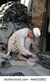 PESHAWAR, PAKISTAN - May 24: A Young Child his remade a Old tires Market workshop, on 24 May, 2016 Peshawar