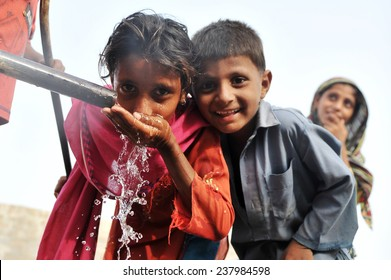 PESHAWAR, PAKISTAN, SEPT 19: Flood affected women and children fill their drinking water coolers at drinking water tank at flood affectees relief camp on September 19, 2010 in Peshawar, Pakistan