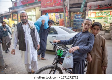 PESHAWAR, PAKISTAN - Sept 27 ,2018:  boy on bicycle is posing for picture while man is holding cigarette  27 Sept, 2018 qissa khwani Peshawar