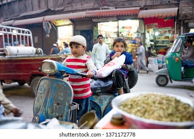 PESHAWAR, PAKISTAN - Sept 27 ,2018:  baby boy and girl are waitng for his father to come out ,male boy is acting like he is riding a scooter 27 Sept, 2018 qissa khwani Peshawar