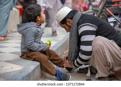 PESHAWAR, PAKISTAN - Sept 27 ,2018:  father is making shoe for his boy  27 Sept, 2018 qissa khwani Peshawar