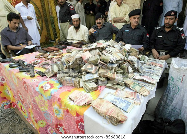 PESHAWAR, PAKISTAN - SEPT 29: Policemen seized weapons, bullets and cash which were recovered from possession of arrested dacoits, during press conference on September 29, 2011in Peshawar.