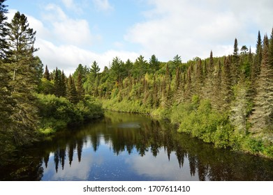 Peshekee River in Upper Peninsula of Michigan with reflection of forest and sky.