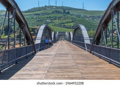 Peso da Regua Portugal - 10 02 2020 : View at the metallic bridge over Douro river on the Peso da Regua downtown, with tourist people strolling
