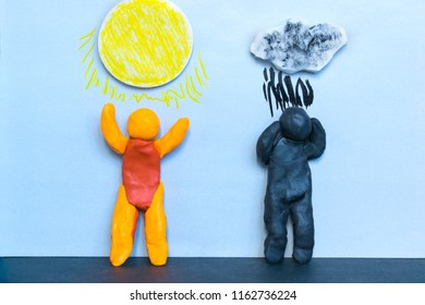 Pessimism and optimism concept, sad and happy plasticine men under the cloudy and sunny sky.