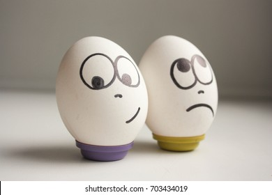 Pessimist and optimist concept. Eggs with painted face. photo for your design