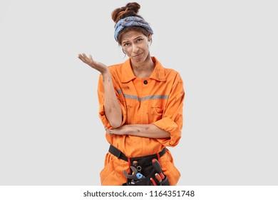 Pessimistic discontent hopeless plumber regrets something, wears orange dirty uniform, makes regreting gesture, poses alone against white background. Crestfallen exasperate female carpenter.