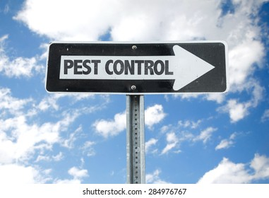 Pest Control direction sign with sky background