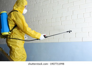 Pest control worker in protective suit spraying pesticide indoors