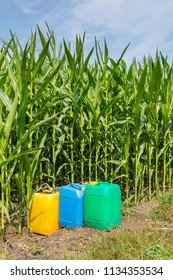 Pesticides in colored jerry cans at field with corn plants