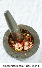 A pestle and mortar with crushed chili