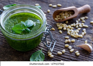Pesto genovese - traditional Italian green basil sauce with pine nuts, basil and garlic on rustic wooden background.