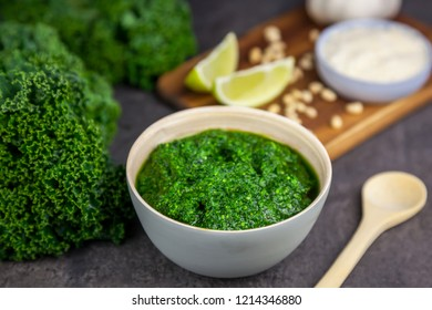 Pesto from kale. Kale, cheese, lemon, pine nuts and garlic on the background
