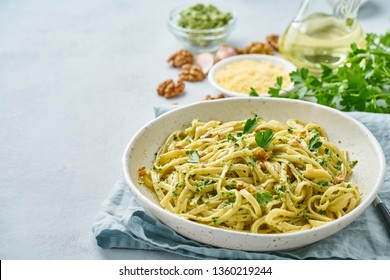 Pesto pasta bavette with walnuts, parsley, garlic, nuts, olive oil. Side view, copy space, blue background