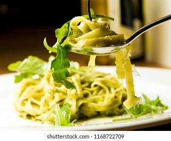 Pesto pasta with fresh rucola on italian restaurant table