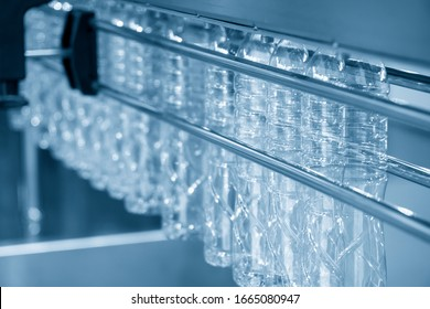 The PET bottles hanging on  the rail on the conveyor belt for filling process in the drinking water factory. The drinking water factory production process by automatic filling machine in the plant.