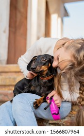Pet care concept. Young woman hugging her dachshund dog outdoors
