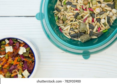 Pet care, veterinary concept. A turquoise plastic bowl with food for rodents- seeds and grains and a bowl of dry veggies on a white table. Close up