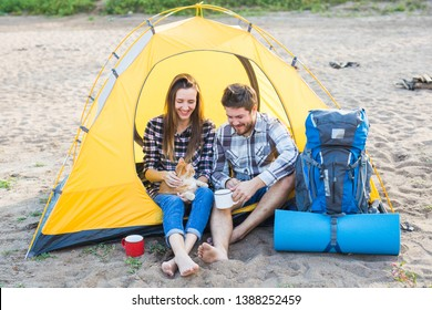 Pet, summer tourism and nature concept - young couple sitting with cat near a tent