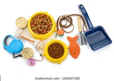 Pet supplies on white background, top view. Leash, brush, scoop, toys and food. Essentials to keep your animal happy and healthy.