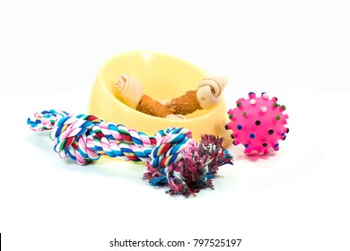 Pet supplies set about plastic bowl, rope, rubber toys with snack bone for dog or cat on white background.