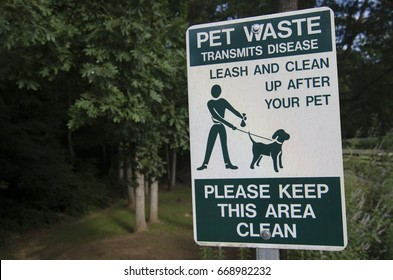 Pet waste sign reminding owner to clean up after their pets