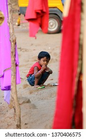 Peta, India – February 28, 2019: Portrait of a child between colored fabrics